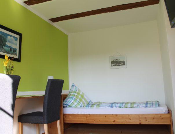 Einzelbett im Zweibettzimmer mit TV-Ausschnitt